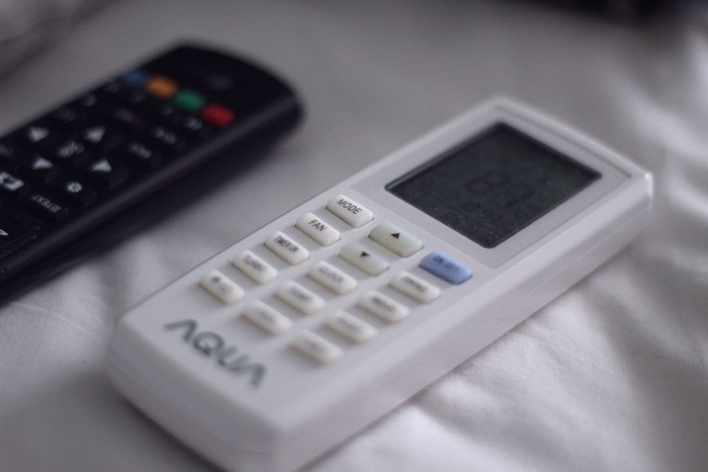 A white remote control for an air conditioner.