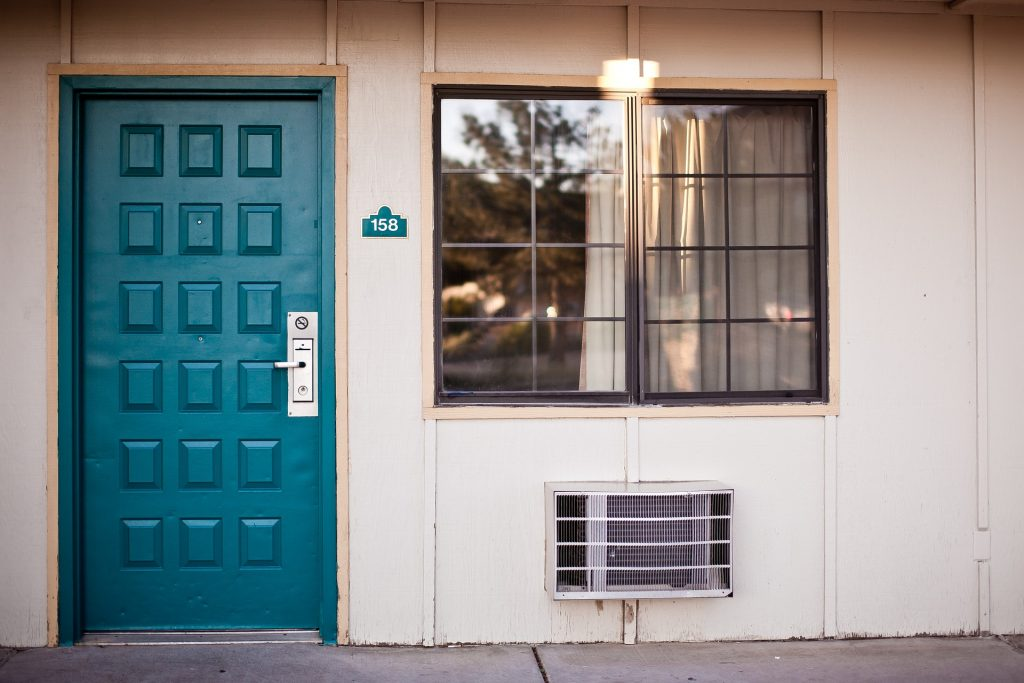 An air conditioning unit underneath a window beside a blue door. Used to show Phoenix air conditioning services.