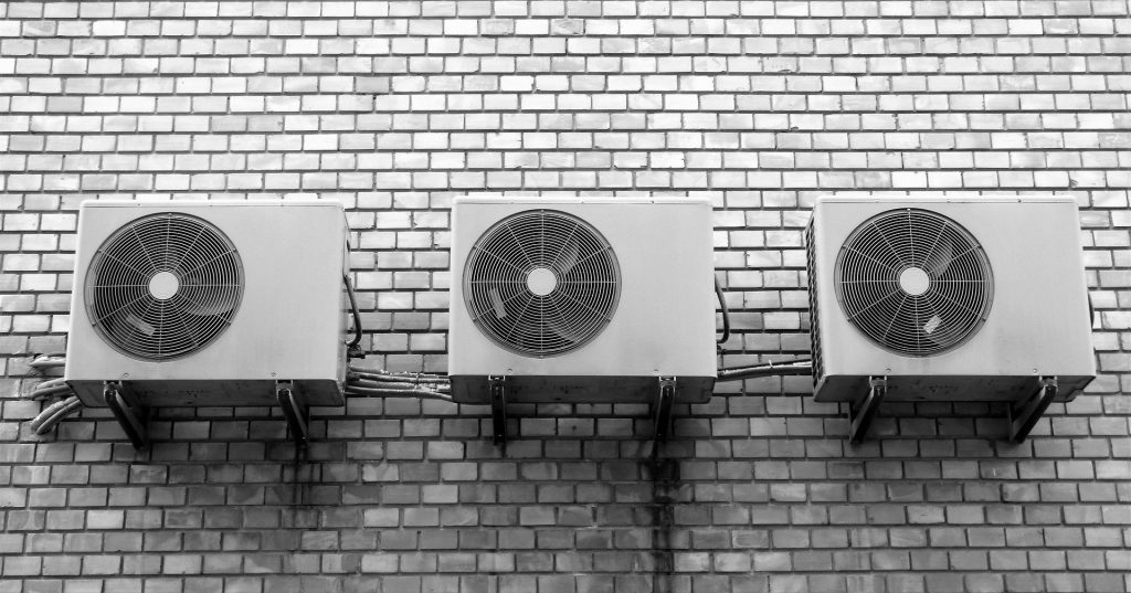 "A row of air conditioners used to reference the concept of ""how to clean your air conditioner filter."""