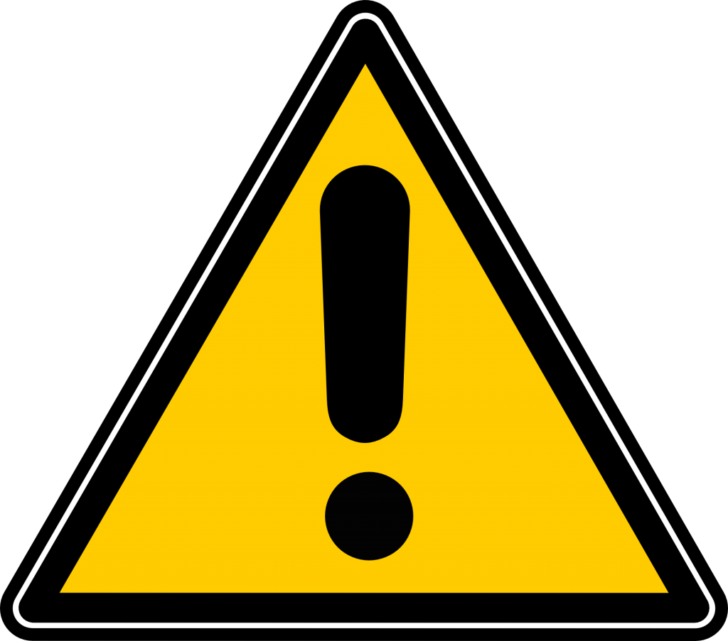 A caution sign representing the importance of safety when learning how to put Freon in an AC unit.