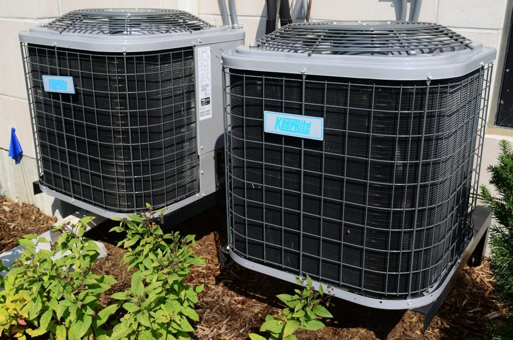 A pair of noisy air conditioner compressors.