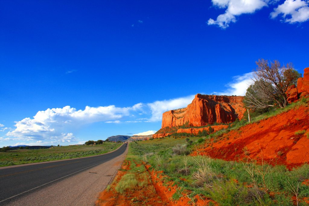A gray highway framed by a Butte of red stone, blue sky above.