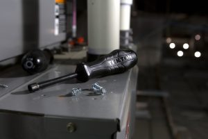 A black screwdriver sits on an HVAC unit that is being repaired.