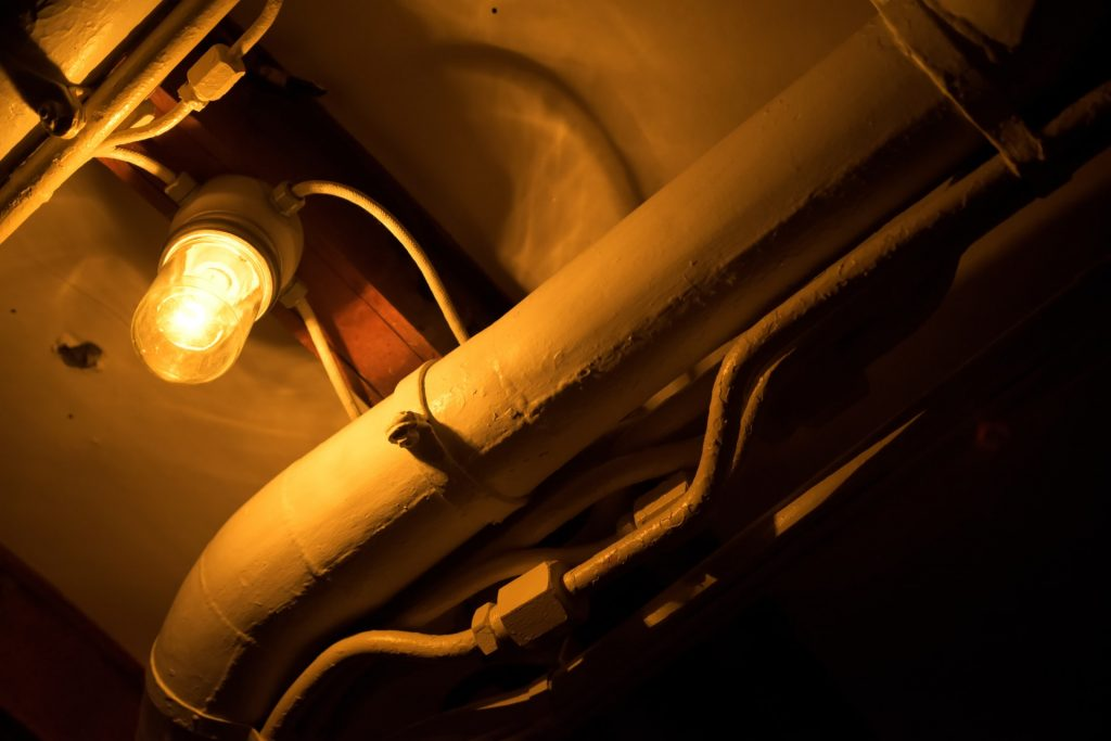 Heating and Electrical Conduits illuminated by a industrial light fixture